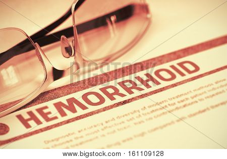 Hemorrhoid - Printed Diagnosis with Blurred Text on Red Background with Pair of Spectacles. Medicine Concept. 3D Rendering.