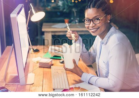 Portrait of businesswoman holding noodles box while sittting in office