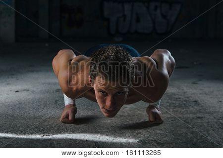 Man pushing up on his fists and looking at camera. Horizontal indoors shot