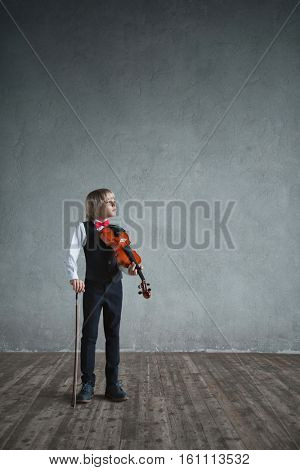 Little boy with a violin in studio