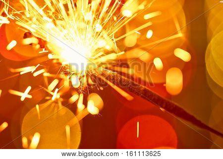 Sparkler close up on color bokeh background