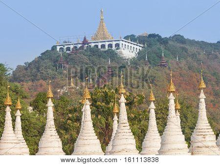 Sutaungpyai Temple on Mandalay Hill seen through Sandamuni Pagoda stupas tops in Mandalay city, Myanmar