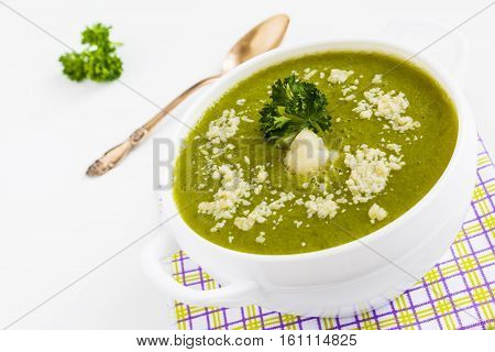 Homemade diet cream soup of cauliflower and green beans. Served in a white bowl sprinkled with grated Parmesan cheese decorated with fresh parsley.