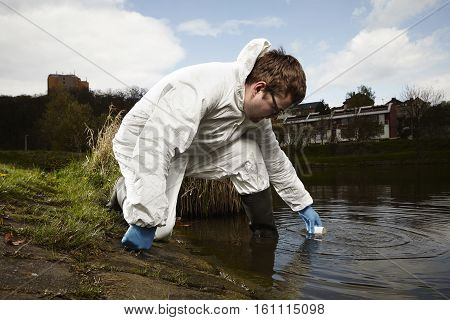 Man in overall protective suit collecting samples of water