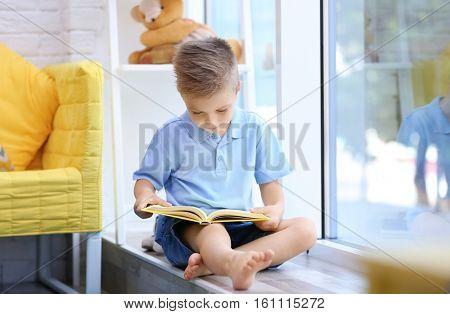Cute boy reading interesting book on windowsill