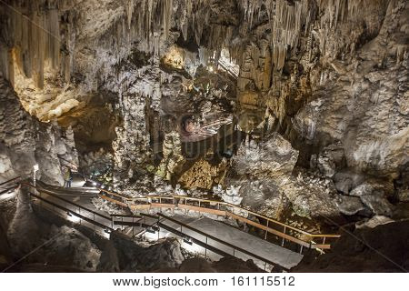 Unidentified visitor admiring stalactites and stalagmites in the Famous Magnificent Nerja Caves