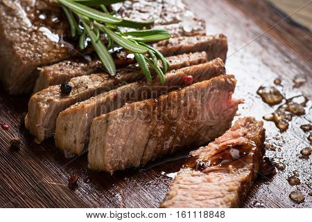 Sliced beef steak medium rare with balsamico and rosemary.