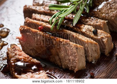 Sliced beef steak medium rare with balsamico and rosemary. Grilled meat.
