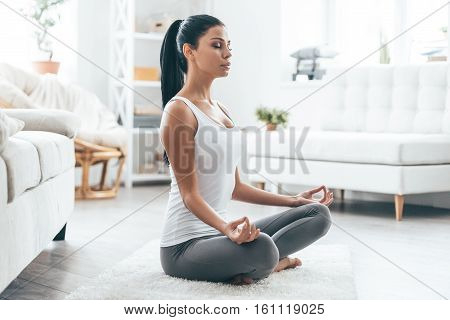 Time for yoga. Attractive young woman exercising and sitting in yoga lotus position while resting at home