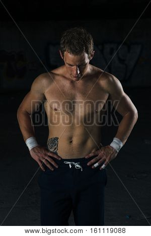 Muscle sportsman holding hands on his waist. Vertical indoors shot