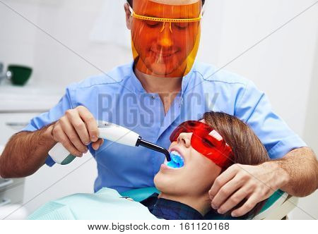 Male dentist treating female's molar with ultraviolet light in clinic. Young woman sitting in chair with open mouth wearing protective glasses.