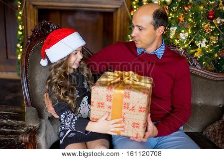 Father and daughter with Christmas gift sitting on the sofa near the Christmas tree. Christmas and New Year interior