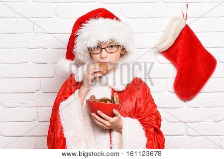 young cute santa claus boy with glasses in red sweater and new year hat with decorative christmas or xmas stocking or boot holding chocolate ?hip cookies in bowl on white brick wall background