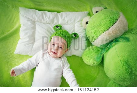 little boy in knitted animal hat lying on soft green blanket with frog softtoy. Cute 5 month old baby on the pillow in bed