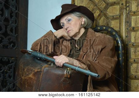 senior woman Bandit with gun in the wild west