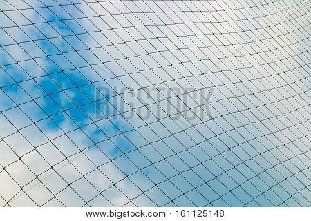 Background of soccer goal nets against blue sky