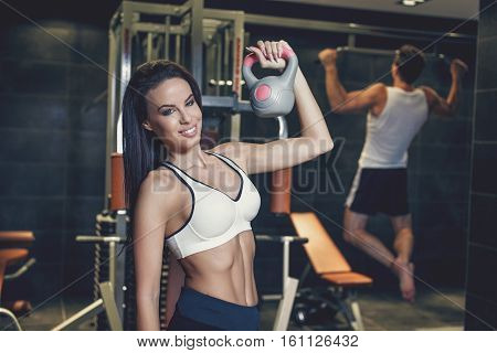 Young couple workout in gym woman posing with kettlebell man doing pull ups
