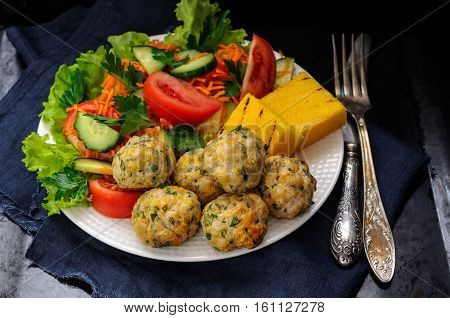 Polenta Grill With Chicken Meatballs And Fresh Vegetables On A White Plate