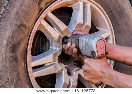 Auto mechanic removing the wheel with an air gun to recap.