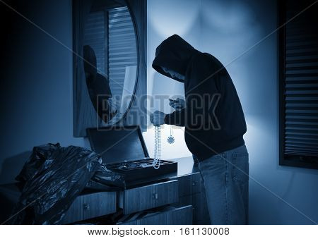 Hooded burglar ransacking a jewelry box in a home