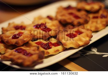 Ruddy waffles with raspberry jam on a plate