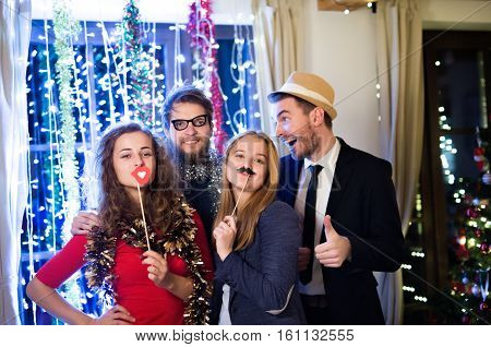 Beautiful hipster friends with photobooth props celebrating the end of the year, having party on New Years Eve, chain of lights behind them.