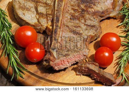 Grilled T bone steak with tomatoes garnished with rosemary on a rustic wooden chopping board