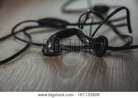 small black earphones in a wooden table