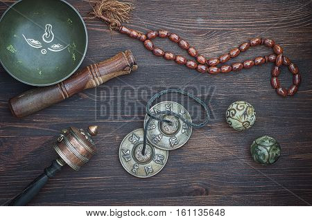 diverse ethnic objects for meditation and relaxation: singing bowl strike plates drums beads and two balls view from above