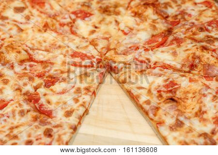 Cheeze pizza with cutout on a wooden board, closeup