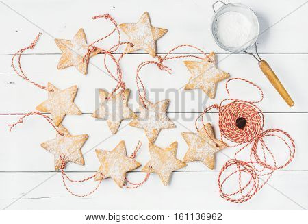 Christmas homemade gingerbread star shaped cookies with sugar powder in sieve and red decoration rope over white wooden background, top view, horizontal composition