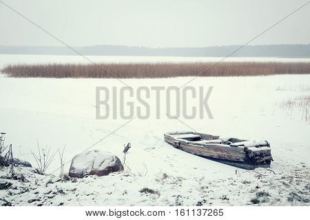 Winter Landscape. Abandoned Frozen Boat on a Lake Covered with Snow. Serenity and Tranquility Concept. Toned Photo with Copyspace.