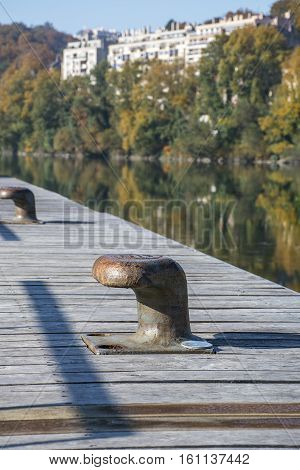 Rowlocks on the pier with river and green trees as background