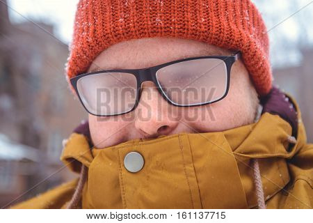 misted glasses of young man outside, winter day