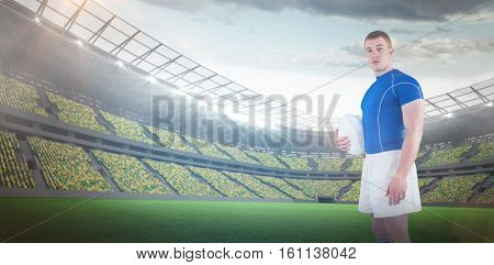 3D Rugby player holding rugby ball against rugby stadium