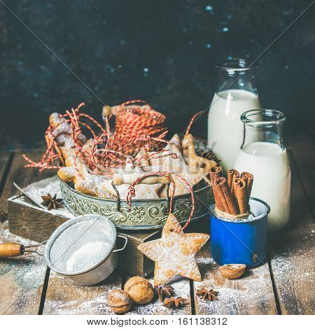 Christmas festive gingerbread cookies in vintage tray, decoration rope, nuts, spices, milk for Santa in bottles, sugar powder. Selective focus, copy space, dark blue plywood background, square crop