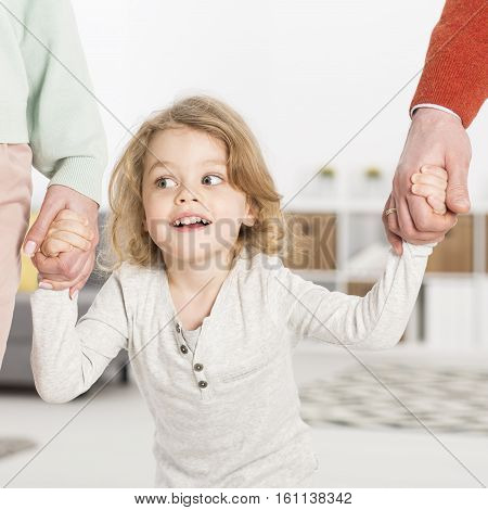 Cheerful Boy Holding Parents Hands