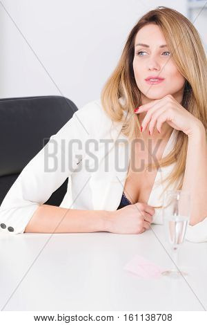 Beautiful young businesswoman sitting in her office and looking seductively poster