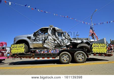 MANDAN, NORTH DAKOTA, July 3, 2016: The 4th of July Rodeo Days 3 day celebration includes the rodeo, Art in the Park, and downtown parade where a wrecked Sheriff's truck is displayed from vehicles not Moving Over to the left lane.
