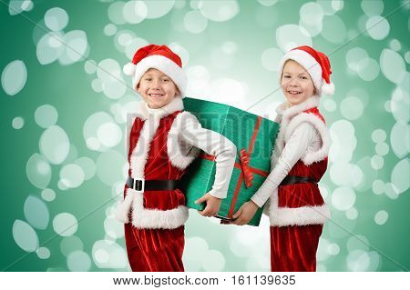 Adorable Happy Boys In Santa Clothes Holding Christmas Gift Box. Isolated On Green Background With L