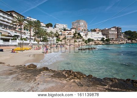 CALA MAYOR BALEARIC ISLANDS SPAIN - OCTOBER 23 2016: People on the beach in bathing suits on a sunny day on October 23 2016 in Cala Mayor Balearic islands Spain.