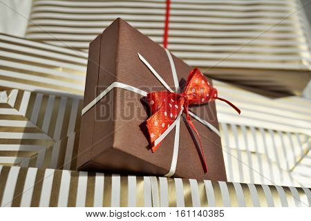Bottom view of heap of gifts (presents) wrapped in lined wrapping paper with white and golden lines with a small brown parcel on the top as a symbol of giving and receiving presents