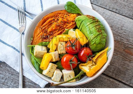 Salad with grilled vegetables: grilled sweet potatoes tomatoes avocados spinach tofu pepper in a white bowl. Perfect for the detox diet or just a healthy meal. Love for a healthy raw food concept.
