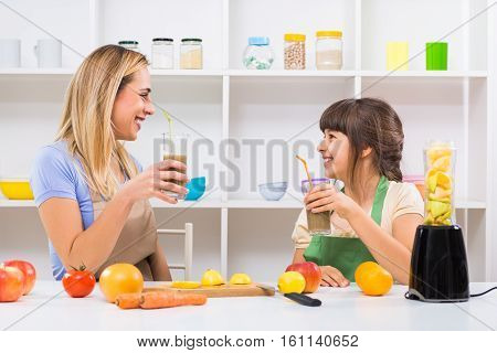 Happy mother and her daughter enjoy making and drinking smoothies together at their home.