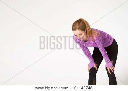Female Taking A Break After Running. Studio Shot, Isolated On White Background. Plenty Of Copy Space