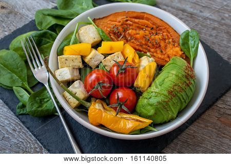 Salad with grilled vegetables: grilled sweet potatoes tomatoes avocados spinach tofu and pepper on dark slate background. Perfect for the detox diet or just a healthy meal. Love for a healthy raw food concept.