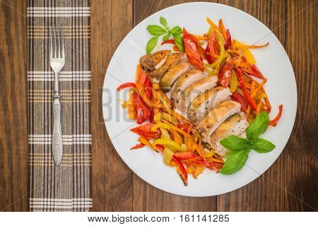 Roast duck breast with vegetable saute on a square plate. Wooden background. Top view