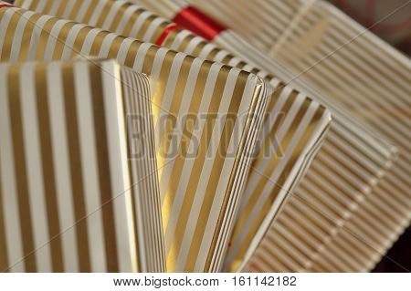 Aerial view of edges of gift packages in white and golden lined wrapping paper as a background symbol of Christmas a Birthday giving and receiving