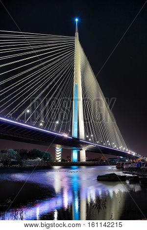 Night view of bridge with colorful reflection of bridge lights on river surface