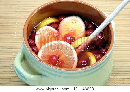 Non-alcoholic drink from cranberries and lemon in big round green pot with wooden spoon inside indoor on brown straw mat top view close up